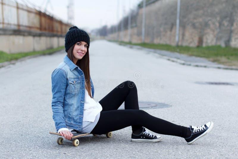 Junges modernes Brunetteskateboardfahrermädchen stockfoto