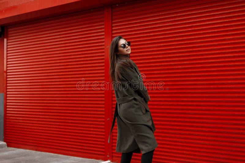 Junges modernes Schönheitsmodell mit Sonnenbrille im modernen grünen Mantel, der nahe dem roten Metalltor aufwirft stockbilder