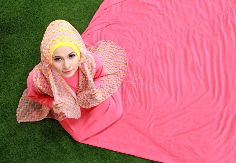 Junges moslemisches Mädchen, das auf Gras sitzt lizenzfreie stockfotografie