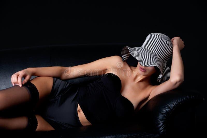 Junges mult etnic Frau im Fünfzigerjahre lingery auf Couch stockbild
