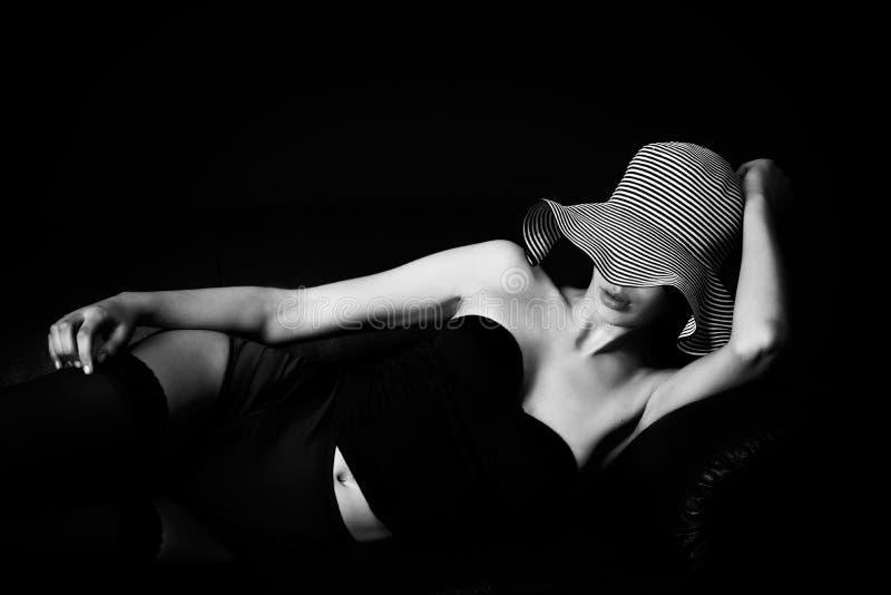 Junges mult etnic Frau im Fünfzigerjahre lingery auf Couch lizenzfreie stockbilder