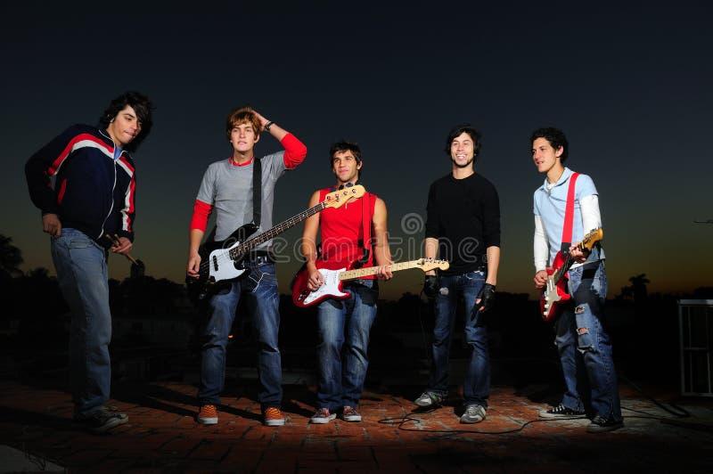Junges musikalisches Band, das an der Dämmerung aufwirft stockfotografie