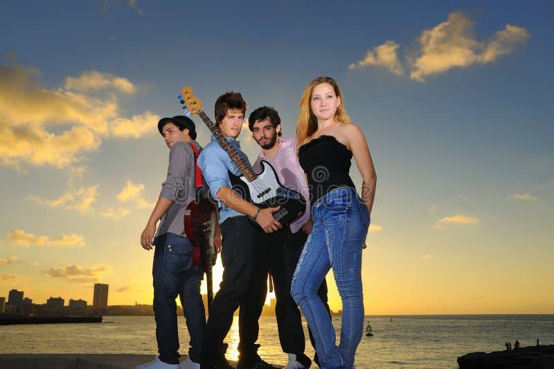 Junges musikalisches Band, das draußen mit Fluglage aufwirft stockfotos