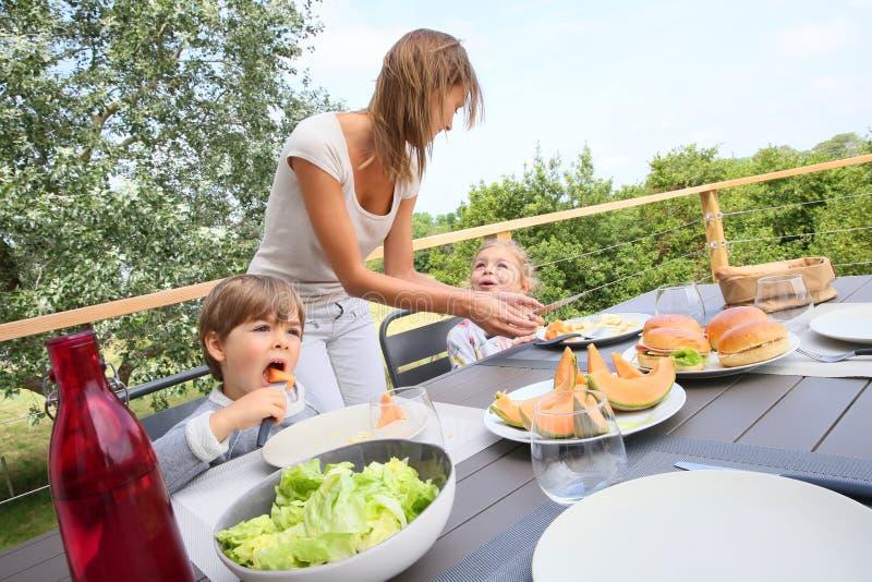 Junges Mutterumhüllungsmittagessen zu den Kindern auf Terrasse lizenzfreie stockbilder