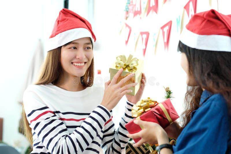 Junges nettes asiatisches Mädchen, das Weihnachtsgeschenkboxen a lächelt und hält lizenzfreie stockbilder