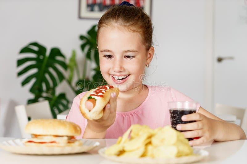 Junges nettes europäisches Mädchen im T-Shirt isst ungesundes Lebensmittel wie Hotdog und Chips stockbild