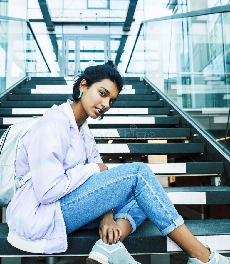 Junges nettes indisches M?dchen am Hochschulgeb?ude, das auf Treppe ein Buch, tragende Hippie-Gl?ser, Lebensstil lesend sitzt stockfoto