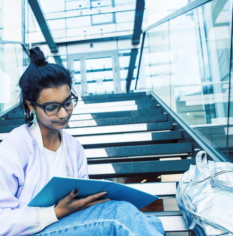 Junges nettes indisches M?dchen am Hochschulgeb?ude, das auf Treppe ein Buch, tragende Hippie-Gl?ser, Lebensstil lesend sitzt stockbild