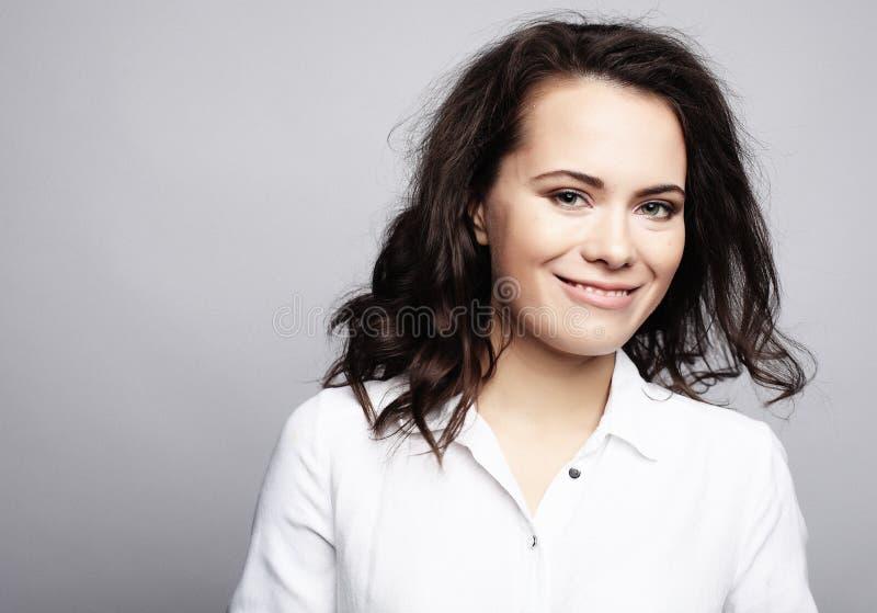 Junges nettes lächelndes Brunettemädchen über weißem Hintergrund lizenzfreies stockfoto