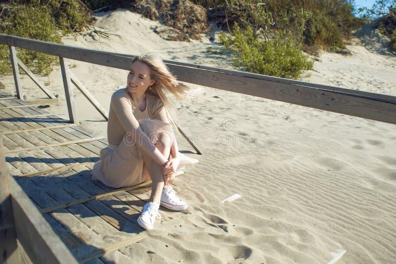 Junges nettes Mädchen auf der Küste Junge Blondine, die auf dem Sand sitzen und das schöne Wetter genießen lizenzfreies stockbild