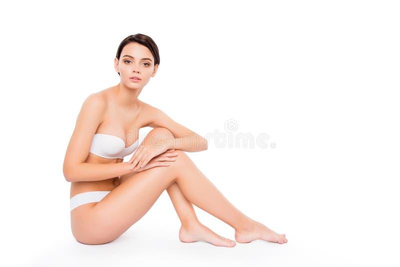 Junges nettes Mädchen, das auf den rührenden glatten Beinen des Bodens sitzt Lokalisiert auf rührender idealer perfekter Haut des lizenzfreie stockbilder