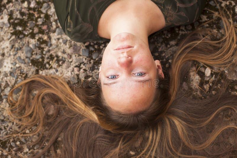 Junges nettes Mädchen, das auf der Pflasterung mit ihrem langen Haar liegt stockbilder