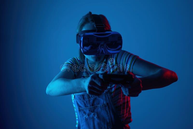 Junges nettes Mädchen, das vr mit gamepad spielt mit kreativem blau-rotem Licht Emocyanally und Spaß Konzeptspiel stockfotografie