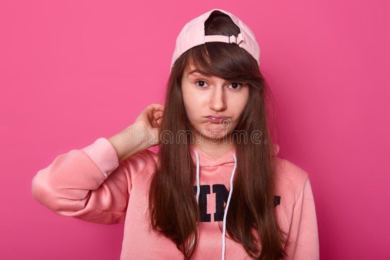 Junges nettes M?dchen in der zuf?lligen Kleidung stieg Hoodie und Maskenkappe zur?ck, aufwerfend auf dem rosa Hintergrund, der Ka stockfoto