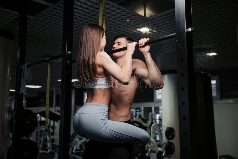 Junges Paar arbeitet an der Turnhalle aus Attraktive Frau und h?bscher muskul?ser Mann bilden in der hellen modernen Turnhalle au lizenzfreies stockbild