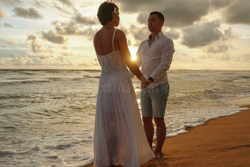 Junges Paar in der Liebe auf einem romantischen Datum trifft den Sonnenuntergang auf dem Strand lizenzfreie stockfotografie