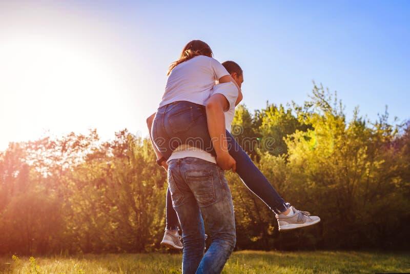 Junges Paar in der Liebe, die Mann Wald des Spaßes im Frühjahr hat, reitet seine Freundin an zurück bei Sonnenuntergang stockfoto