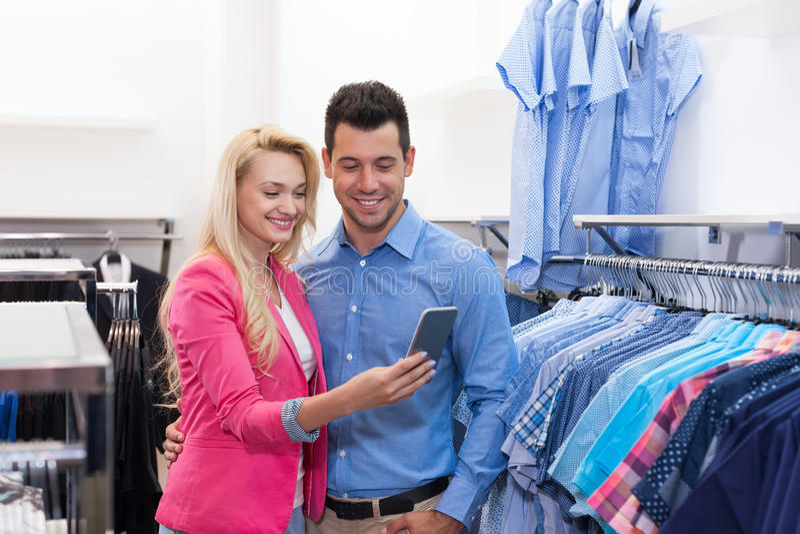 Junges Paar-Einkaufen, glücklicher lächelnder Mann und Frauen-Gebrauchs-Zellintelligenter Telefon-Kunden-in Mode Shop, die Kleidu lizenzfreie stockfotografie