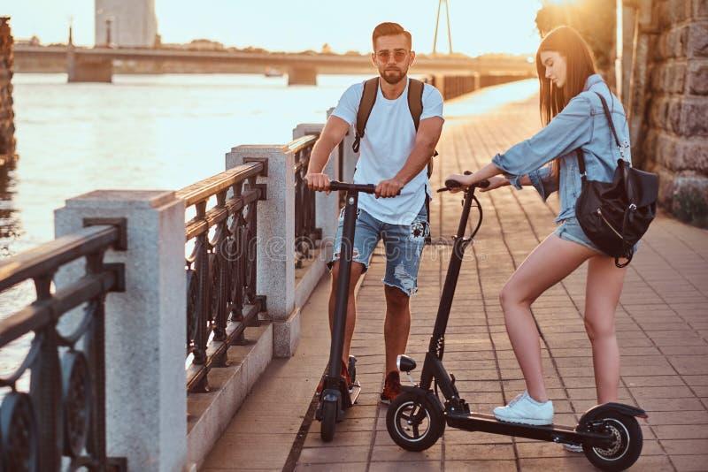 Junges Paar genießt das Reiten des Elektrorollers lizenzfreie stockbilder