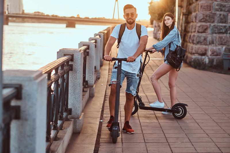 Junges Paar genießt das Reiten des Elektrorollers stockfoto