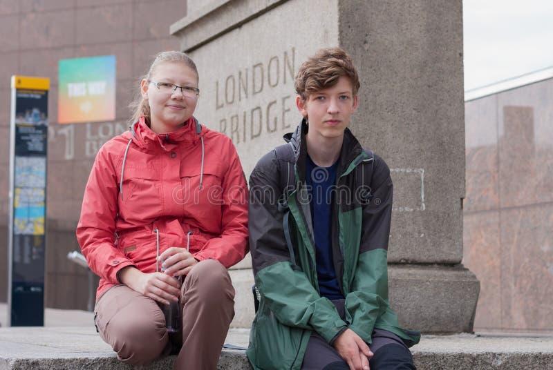 Junges Paar sitzt unter Steinsockel London-Brücke in Lo lizenzfreies stockfoto