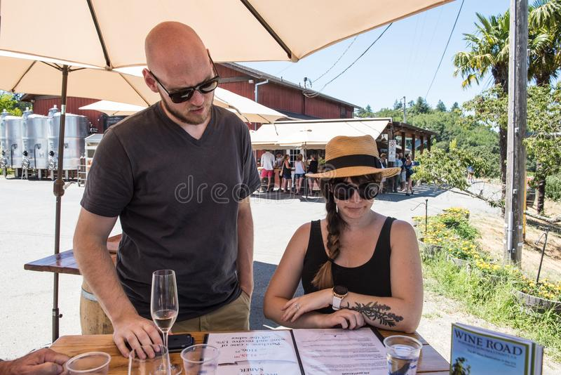 Junges Paar studiert die Weinliste bei einem Napa Valley, CAWine-Probieren stockbild