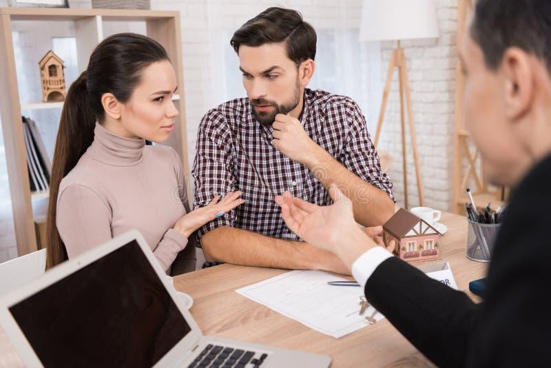 Junges Paar trifft Entscheidungen betreffend den Kauf des Hauses sitzend im Büro der Immobilienagentur lizenzfreies stockfoto