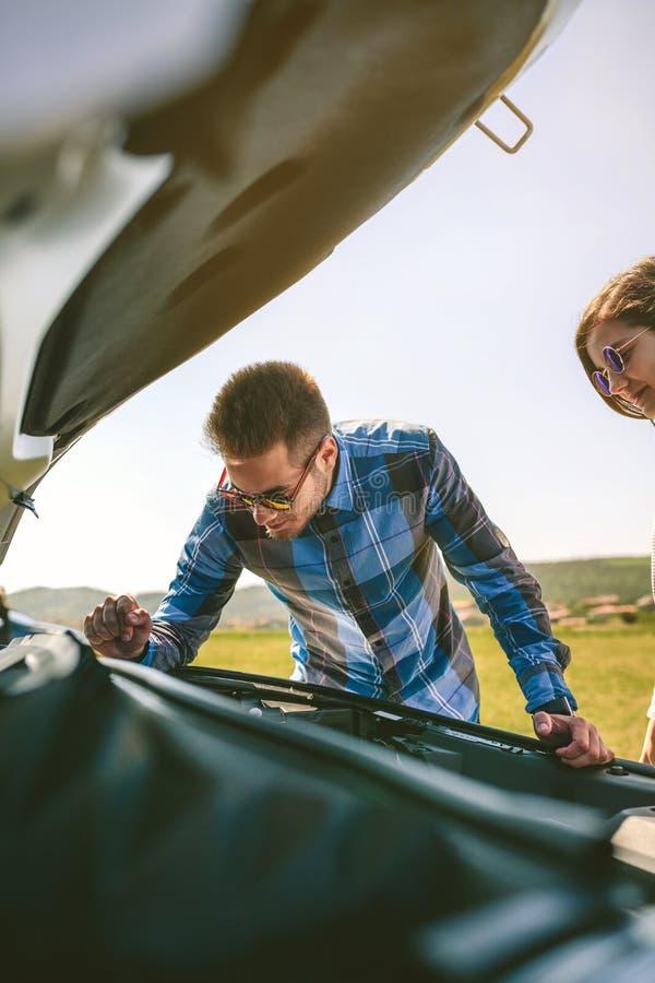 Junges Paar versucht, das aufgegliederte Auto zu reparieren lizenzfreies stockbild