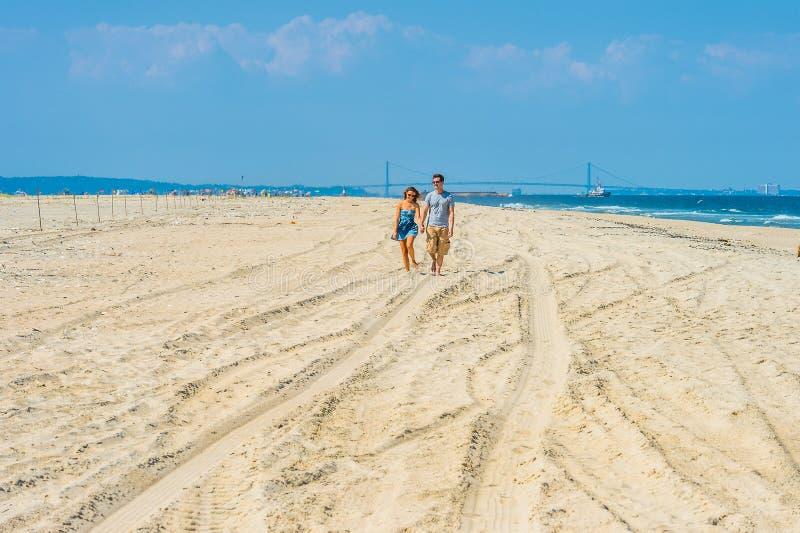 Junges Paargehen, entspannend auf dem Strand in New-Jersey, USA stockbilder