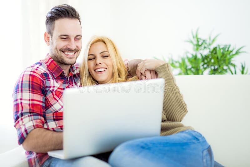 Junges Paargraseninternet zu Hause, unter Verwendung des Laptops und des Lächelns lizenzfreies stockbild