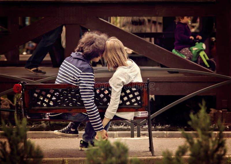 Junges Paarhändchenhalten auf Bank im Park lizenzfreie stockfotos