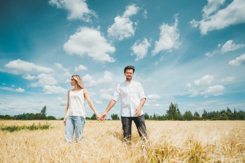 Junges Paarhändchenhalten beim Gehen durch Feld vor dem hintergrund des blauen Himmels stockbild