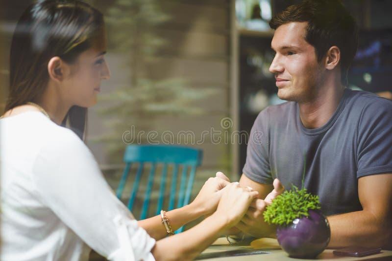 Junges Paarhändchenhalten im Café lizenzfreie stockbilder