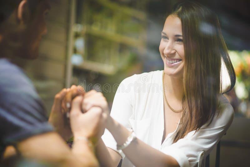 Junges Paarhändchenhalten im Café stockfotografie
