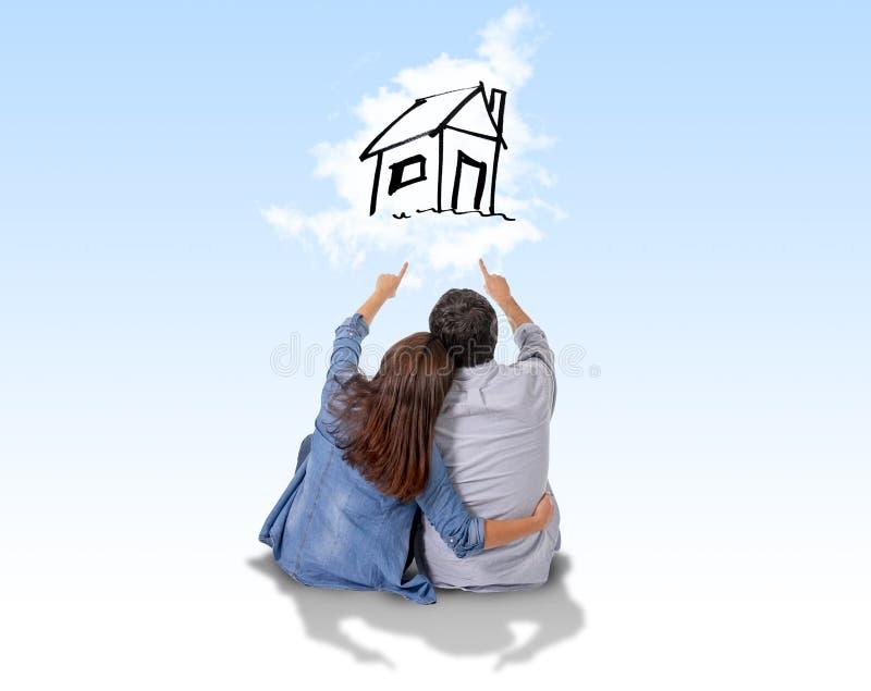 Junges Paarträumen und -darstellung ihr neues Haus im wirklichen Zustand lizenzfreie abbildung