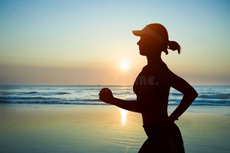 Junges Passung und attraktive Frau in amerikanisches Kappentraining auf dem Sonnenuntergangstrand, der herein laufendes Eignungst lizenzfreie stockbilder