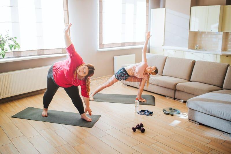 Junges Plus-sixe Modell und dünne Frau, die zusammen im Wohnzimmer ausdehnt und trainiert Stellung in der Yogahaltung Eine Hand stockbild