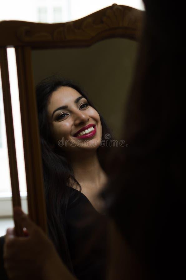 Junges reizend Brunettemädchen betrachtet ihre Reflexion im Spiegel stockfoto
