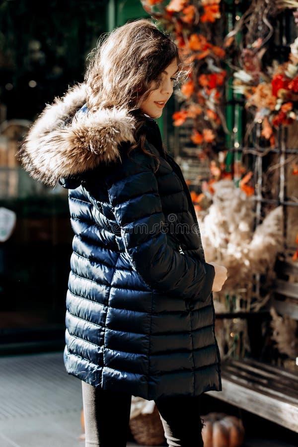 Junges reizend Mädchen in einer unten Jacke mit einem Pelzkragen, der in einem Park an einem sonnigen Tag aufwirft lizenzfreie stockbilder