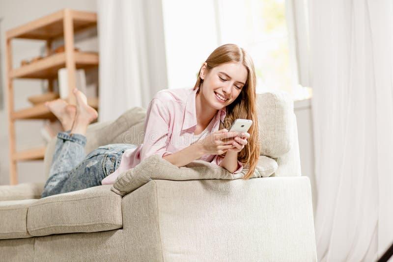 Junges reizend Mädchen, entspannend auf dem Sofa und schicken einem Freund sms lizenzfreie stockfotos