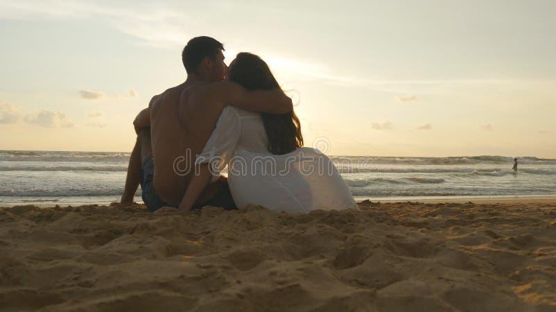 Junges romantisches Paar genießt den schönen Sonnenuntergang, der auf dem Strand und dem Umarmen sitzt Eine Frau und ein Mann sit stockbilder