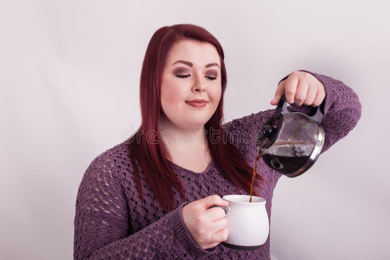Junges Rot ging das weibliche Gießen und das Schauen eines Tasse Kaffees voran lizenzfreie stockbilder