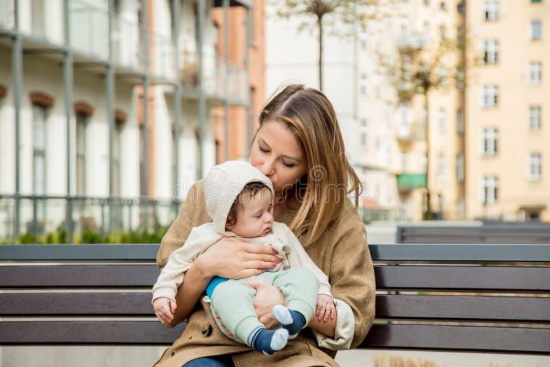Junges Rothaarigemädchen und -kind, die auf Bank sitzt stockfotografie