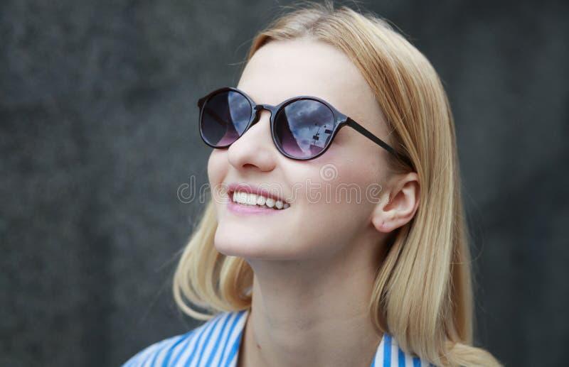 Junges rothaariges Mädchen in der Sonnenbrille mit dunklen Gläsern in einem Rahmen, Tag, im Freien lizenzfreies stockbild