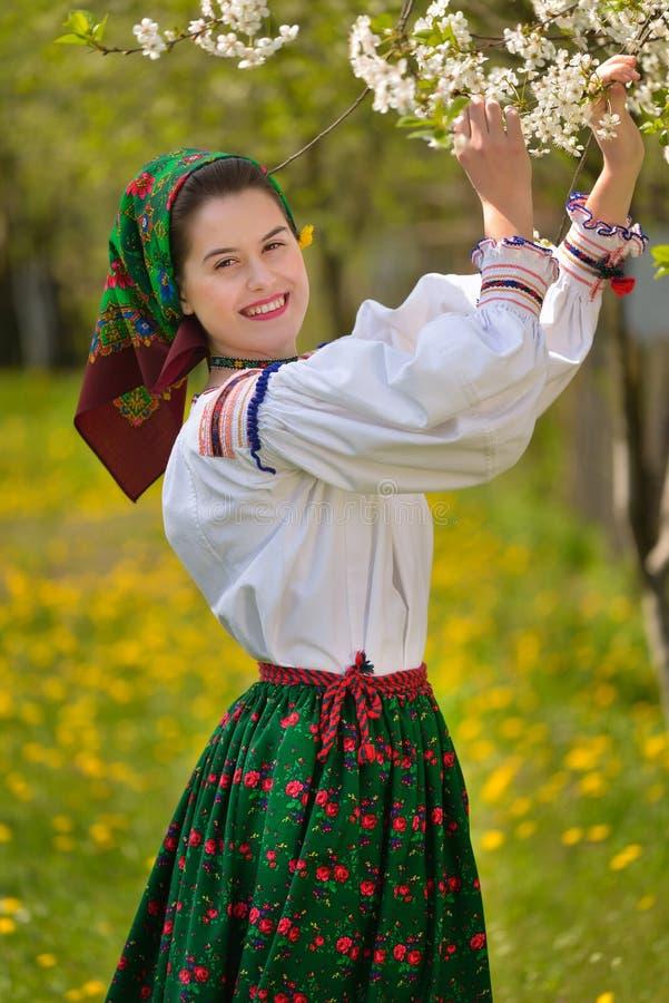 Junges rumänisches Mädchen, das im Frühjahr Zeit mit traditionellem Kostüm lächelt lizenzfreies stockfoto