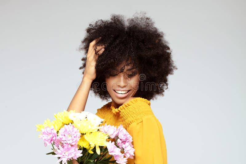 Junges schönes Afromädchen mit Blumen stockfoto
