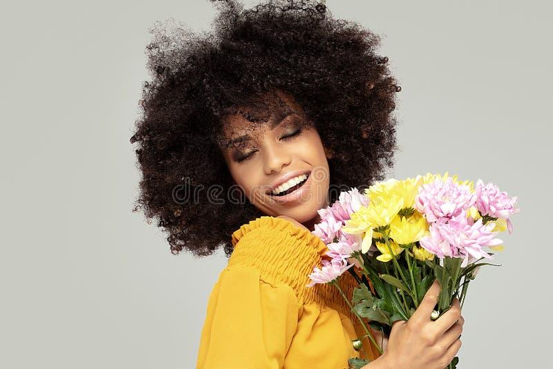 Junges schönes Afromädchen mit Blumen stockfotografie