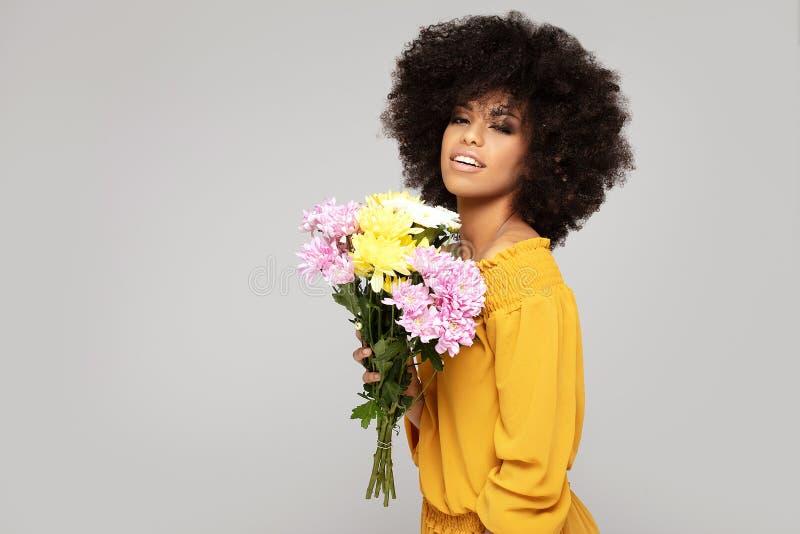 Junges schönes Afromädchen mit Blumen lizenzfreie stockfotos