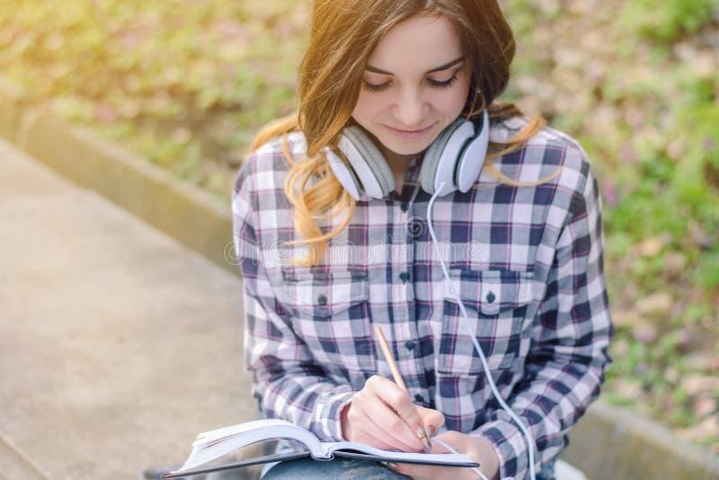 Junges schönes angesporntes Mädchen im karierten Hemd mit Kopfhörern schreibend in ihr Notizbuch Collegeuniversitätsgeländestuden lizenzfreie stockfotografie