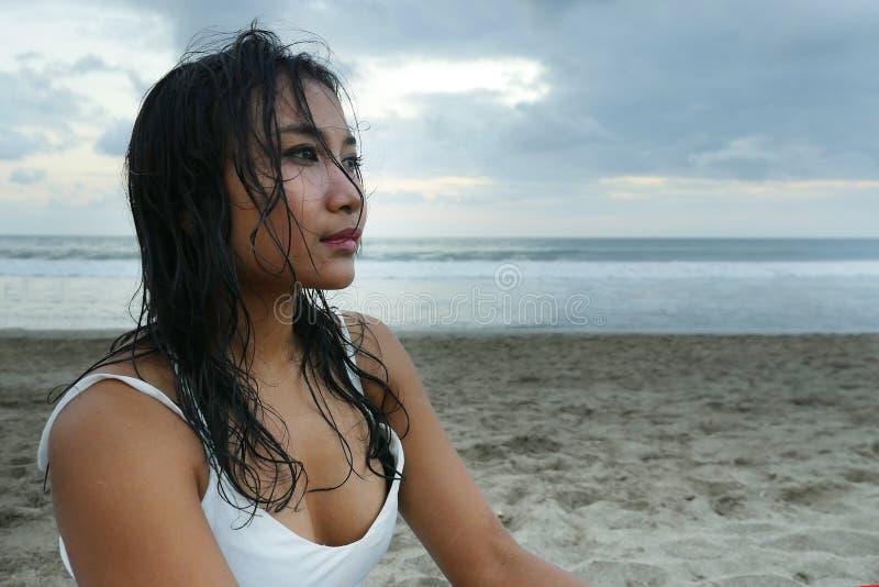 Junges schönes asiatisches Mädchen mit dem nassen Haar am Sonnenuntergangstrand, der im Abstand durchdacht und nachdenklich schau lizenzfreie stockfotografie